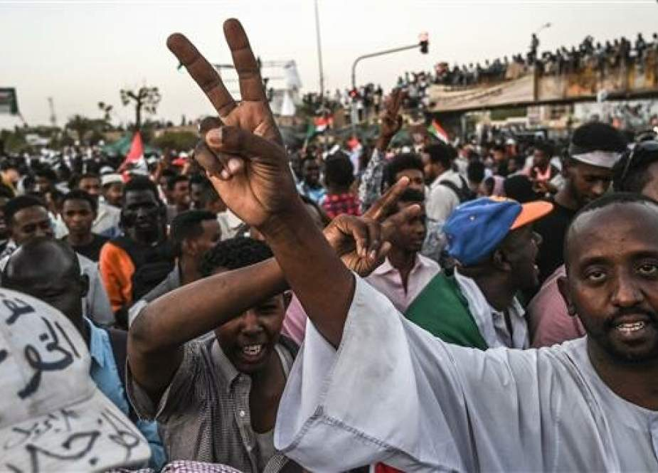 Sudanese protestors shout slogans as they flash victory signs during a protest outside the army complex in the capital Khartoum on April 20, 2019. (Photo by AFP)