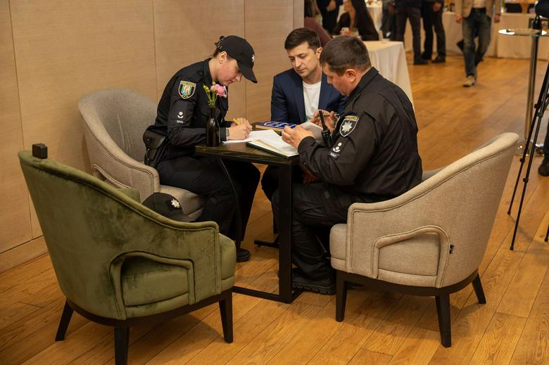 Ukrainian police officers draw out an administrative offense report before handing it over to presidential candidate Volodymyr Zelenskiy, who demonstrated his ballot in public while casting a vote, at his campaign headquarters in Kiev