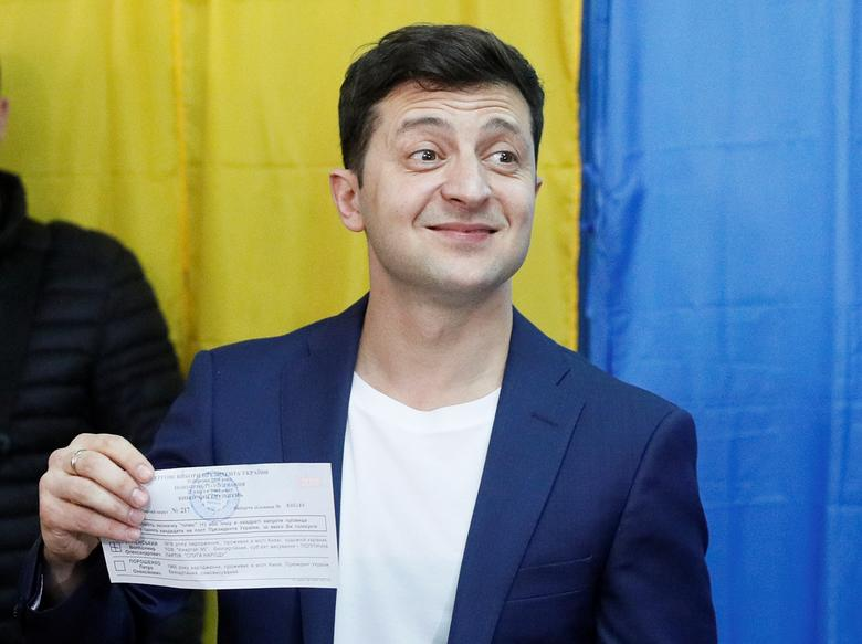 Ukrainian presidential candidate Volodymyr Zelenskiy displays his ballot while standing in front of the media at a polling station during the second round of a presidential election in Kiev