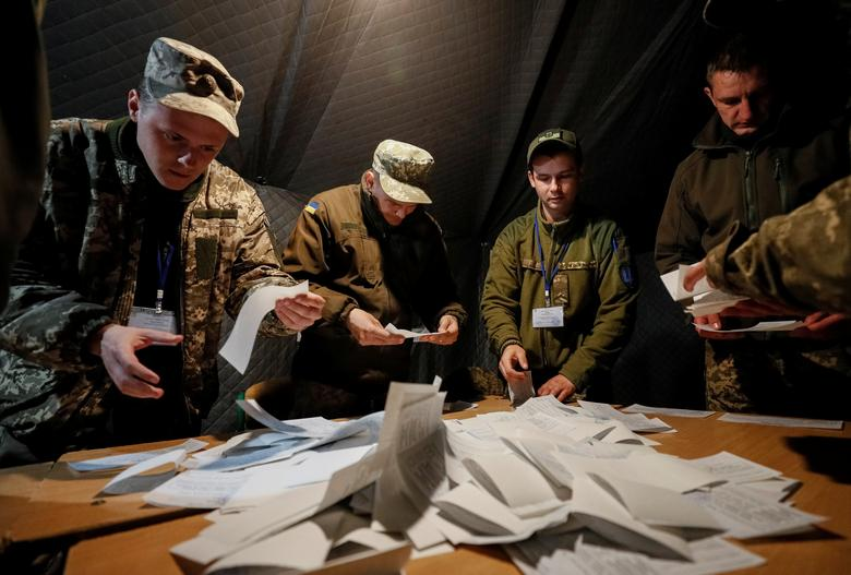 Members of a local electoral commission count votes at a polling station created for servicemen taking part in the government's five-year-old conflict in eastern Ukraine against Kremlin-backed rebels, near the front line, in the village of Zaitseve, Ukra