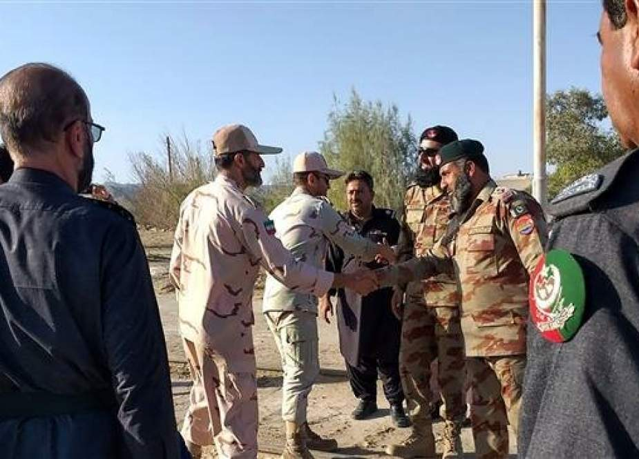 This picture taken on April 21, 2019 shows Iranian border security officials (L) shake hands with Pakistani border security officials at Zero Point in the Pakistan-Iran border town of Taftan. (Photo by AFP)