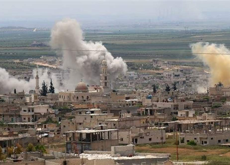 Smoke rises above buildings during shelling by Syrian government forces against the positions of foreign-sponsored Takfiri militants in the town of Khan Sheikhun in the southern countryside of Idlib province on May 11, 2019. (Photo by AFP)