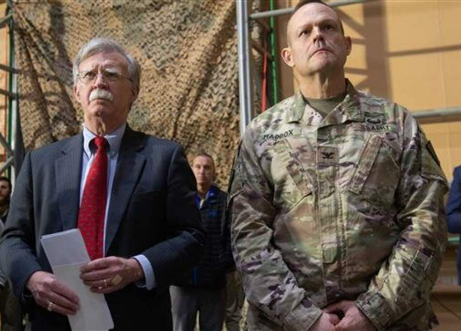 US National Security Adviser John Bolton (L) listens as US President Donald Trump speaks to members of the US military during an unannounced trip to Iraq on December 26, 2018. (File photo)