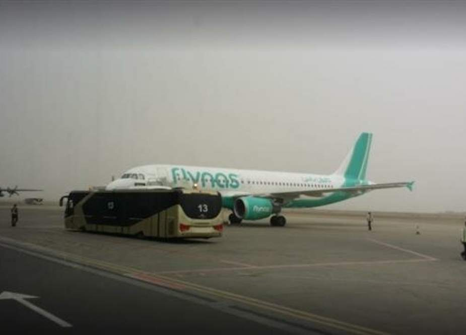 This file picture shows a passenger plane operated by Saudi low-cost airline Flynas as well as a Lockheed C-130 Hercules military transport aircraft on the runway of King Abdullah bin Abdulaziz Airport, Jizan region, Saudi Arabia.