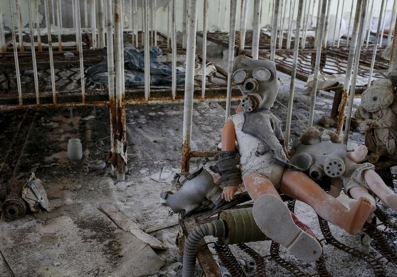 A doll in a children's gas mask amongst beds at a kindergarten in the abandoned city of Pripyat