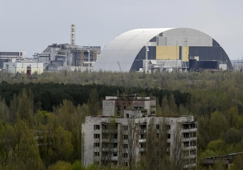 A containment shelter for the damaged fourth reactor (L) and the New Safe Confinement (NSC) structure (R) at the Chernobyl Nuclear Power Plant are seen from the abandoned town of Pripyat