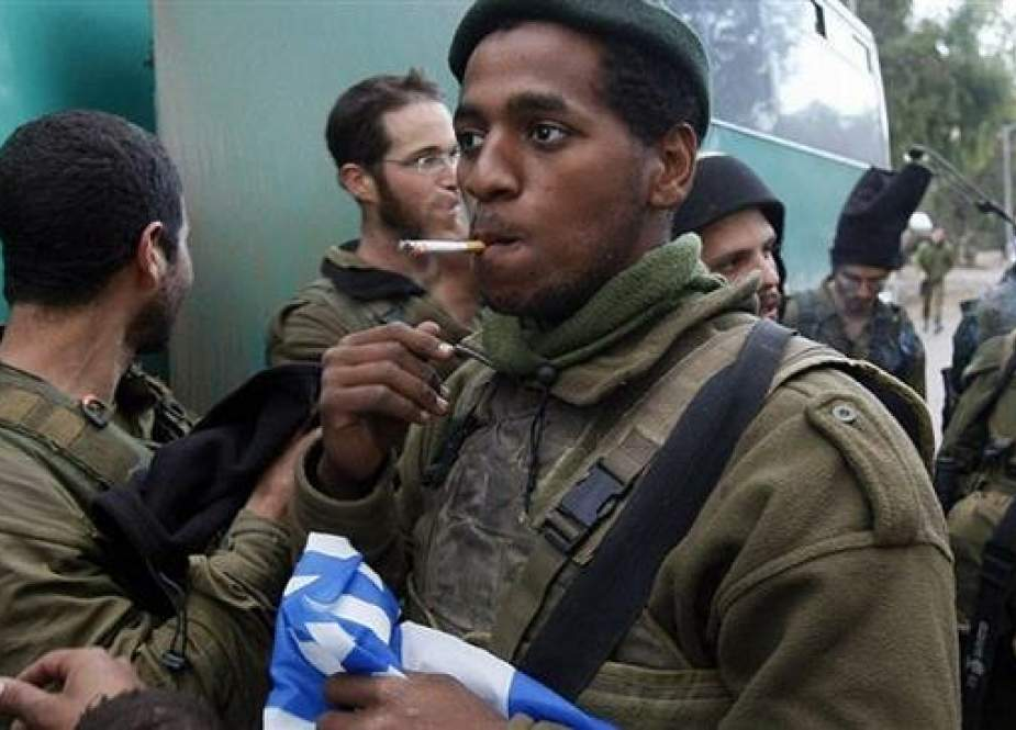 In this file picture, an Israeli soldier holds a flag as he smokes a cigarette near the border between the Gaza Strip and occupied territories. (By AFP)