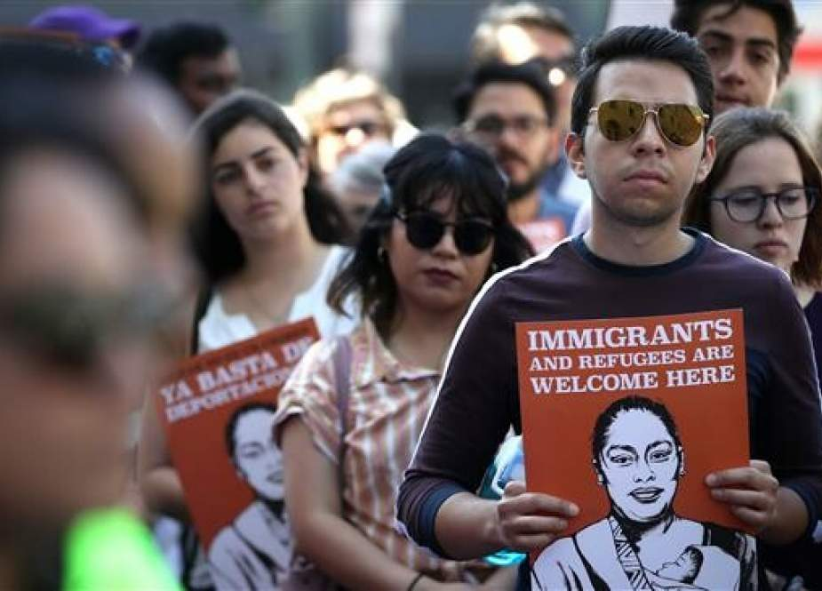 Protesters hold signs during a demonstration in support of restoring protections for asylum seekers in San Francisco, California, on June 11, 2019. (Getty Images)