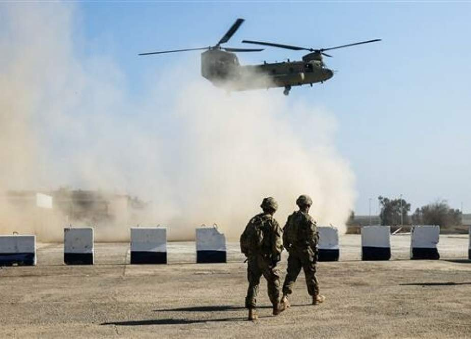File photo shows US troops patrolling as a US Army C-47 Chinook helicopter flies overhead in Iraq.
