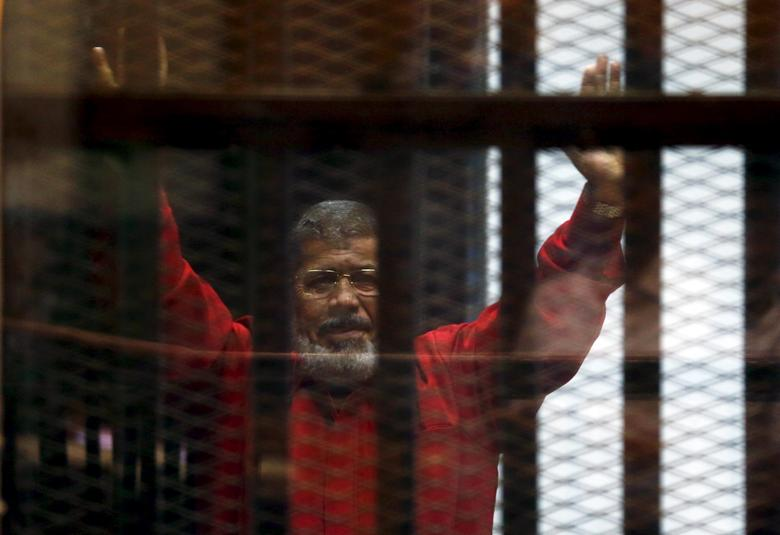 Deposed President Mohamed Mursi greets his lawyers and people from behind bars at a court wearing the red uniform of a prisoner sentenced to death, during his court appearance with Muslim Brotherhood members on the outskirts of Cairo, Egypt, June 21, 201