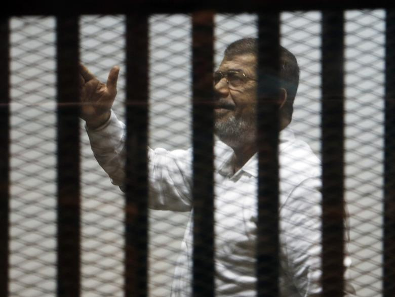 Ousted Egyptian President Mohamed Mursi gestures behind bars during a trial of him and other leaders of the Muslim Brotherhood on charges of spying and terrorism at a court in the police academy on the outskirts of Cairo, November 18, 2014