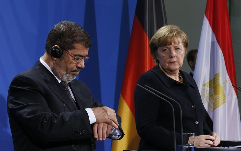 Egyptian President Mohamed Mursi looks at his watch during a joint news conference with German Chancellor Angela Merkel and in Berlin January 30, 2013