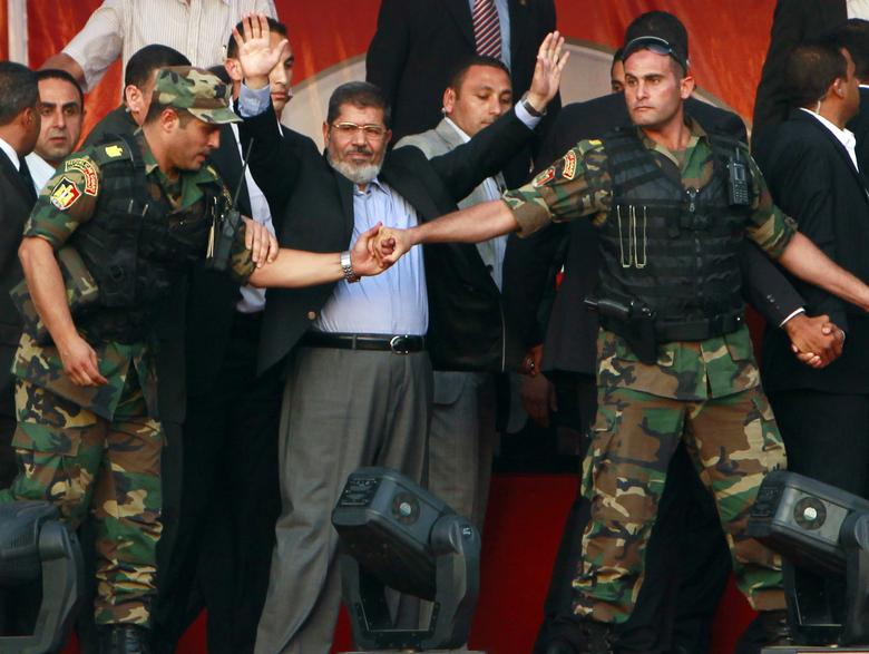 Egypt's Islamist President-elect Mohamed Mursi waves to his supporters while surrounded by his members of the presidential guard in Cairo's Tahrir Square, June 29, 2012