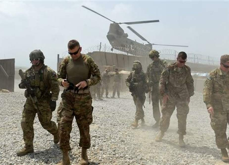 In this AFP file photo taken on August 12, 2015 US army soldiers walk as a NATO helicopter flies overhead in the Khogyani district in the eastern province of Nangarhar.