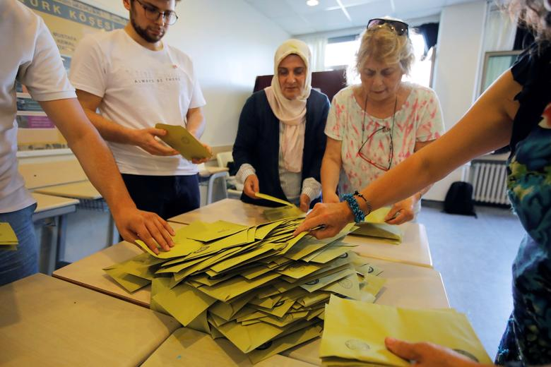 Election officials open a ballot box to count votes at a polling station in Istanbul, June 23