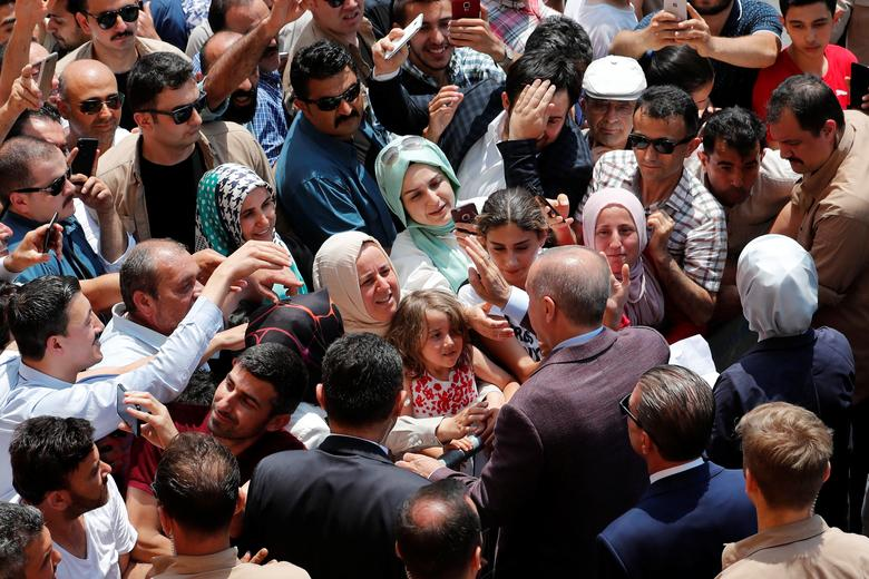 Turkish President Tayyip Erdogan and his wife Emine greet people after casting their ballots, outside a polling station in Istanbul, June 23