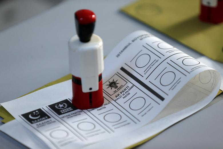 A ballot paper and a stamp are seen at a polling station during a mayoral election re-run in Istanbul, June 23