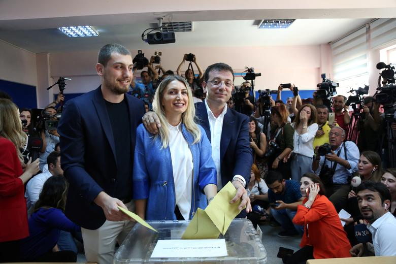 Ekrem Imamoglu, mayoral candidate of the main opposition Republican People's Party (CHP), his wife Dilek and their son Semih cast their ballots at a polling station in Istanbul, June 23