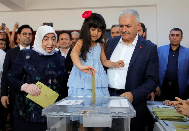Binali Yildirim, mayoral candidate of the ruling AK Party, poses with his wife Semiha and granddaughter casting a ballot at a polling station in Istanbul, June 23