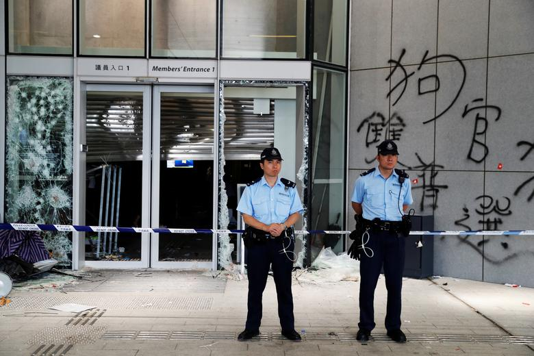Policemen stand in front of graffiti on the walls of the Legislative Council
