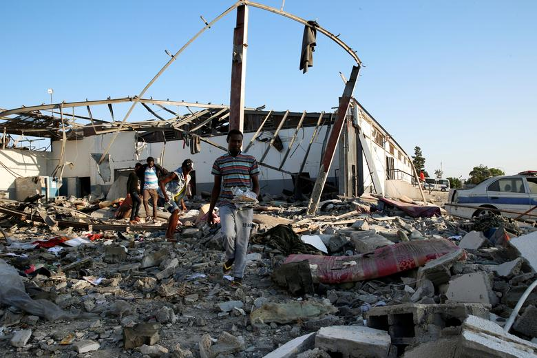 Migrants carry the remains of their belongings from among rubble at a detention centre for mainly African migrants that was hit by an airstrike in the Tajoura suburb of the Libyan capital of Tripoli, Libya July 3, 2019. An air strike hit a detention cent