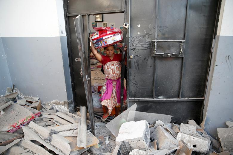 A migrant picks up her belongings from rubble at a detention centre for mainly African migrants that was hit by an airstrike, in the Tajoura suburb of Tripoli, July 3. The hangar-type detention center is next to a military camp, one of several in Tajoura
