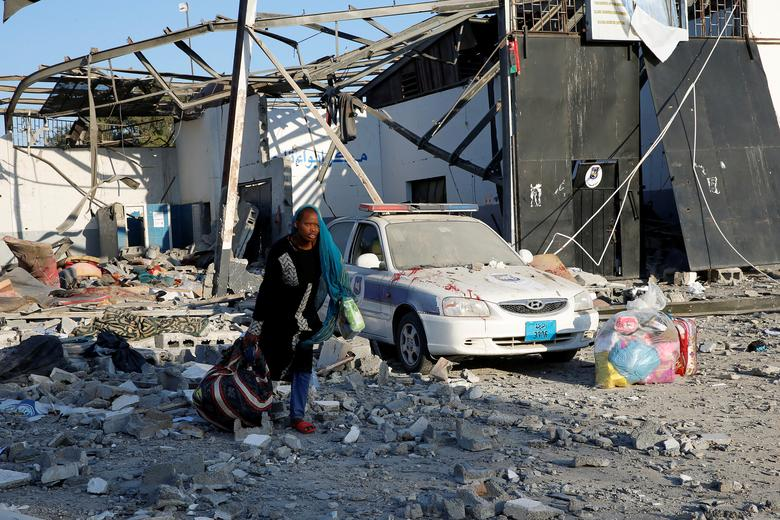 A migrant picks up her belongings from among rubble at a detention centre for mainly African migrants that was hit by an airstrike in the Tajoura suburb of the Libyan capital of Tripoli, July 3