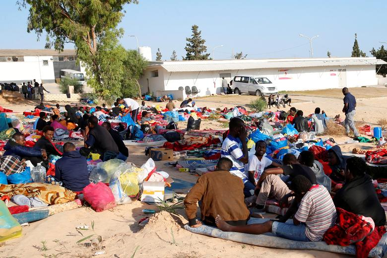 Migrants are seen with their belongings at the yard of a detention centre for mainly African migrants, hit by an airstrike, in the Tajoura suburb of Tripoli, July 3