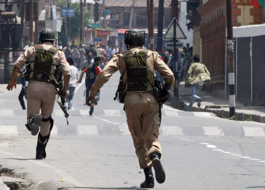 Indian policemen chase Kashmiri protesters in Srinagar.