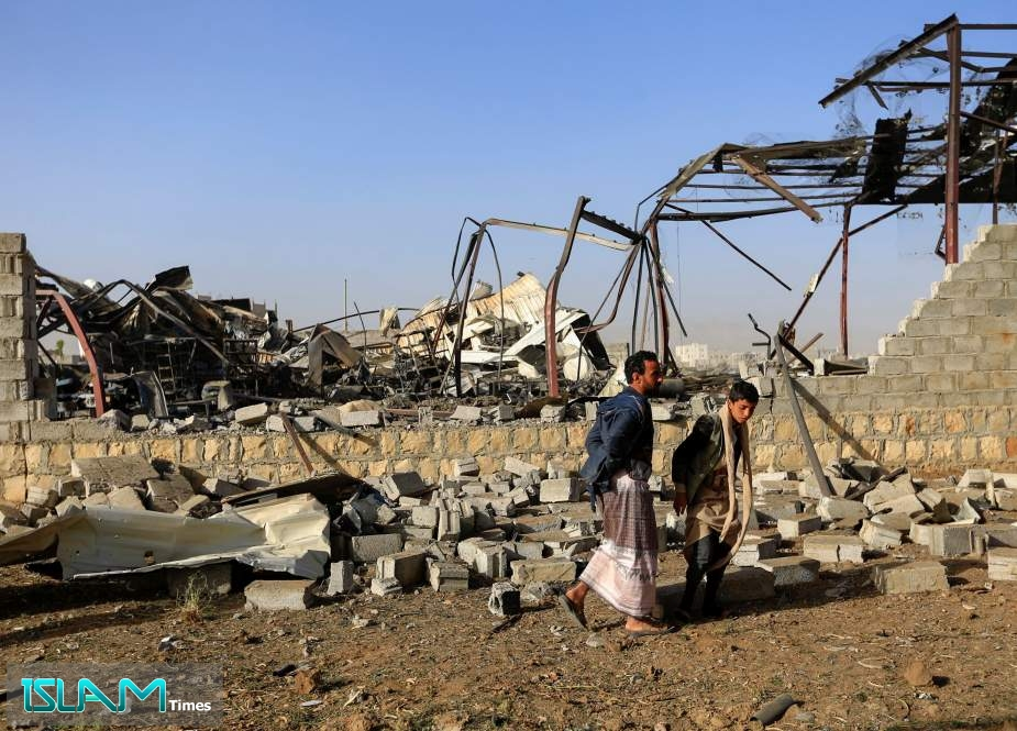 Civilians inspect the damage at a factory after an airstrike by the Saudi-led coalition in the Yemeni capital Sana