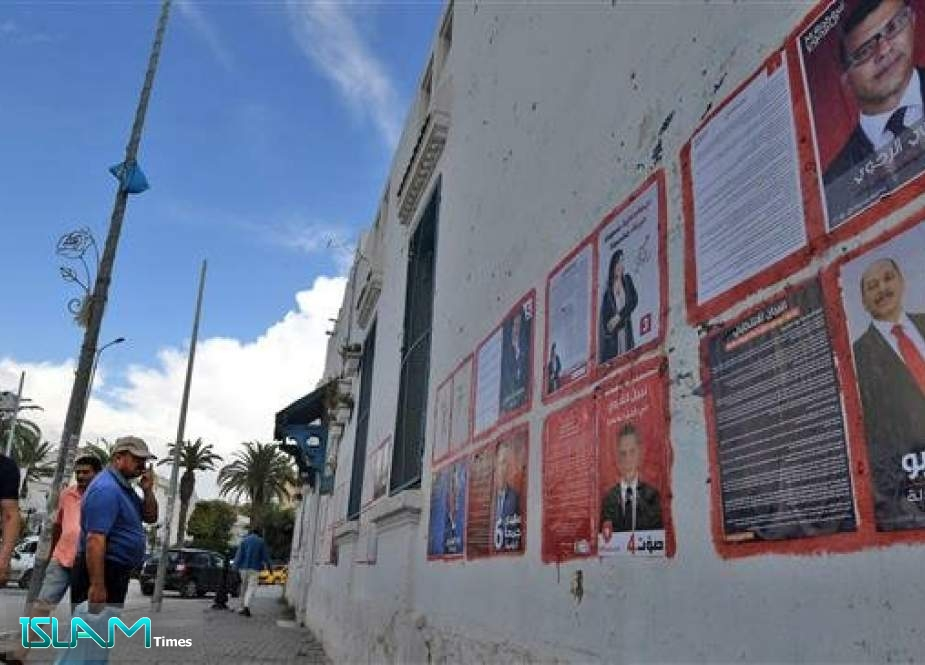 A man looks at posters of Tunisian presidential candidates in the capital Tunis on September 2, 2019.
