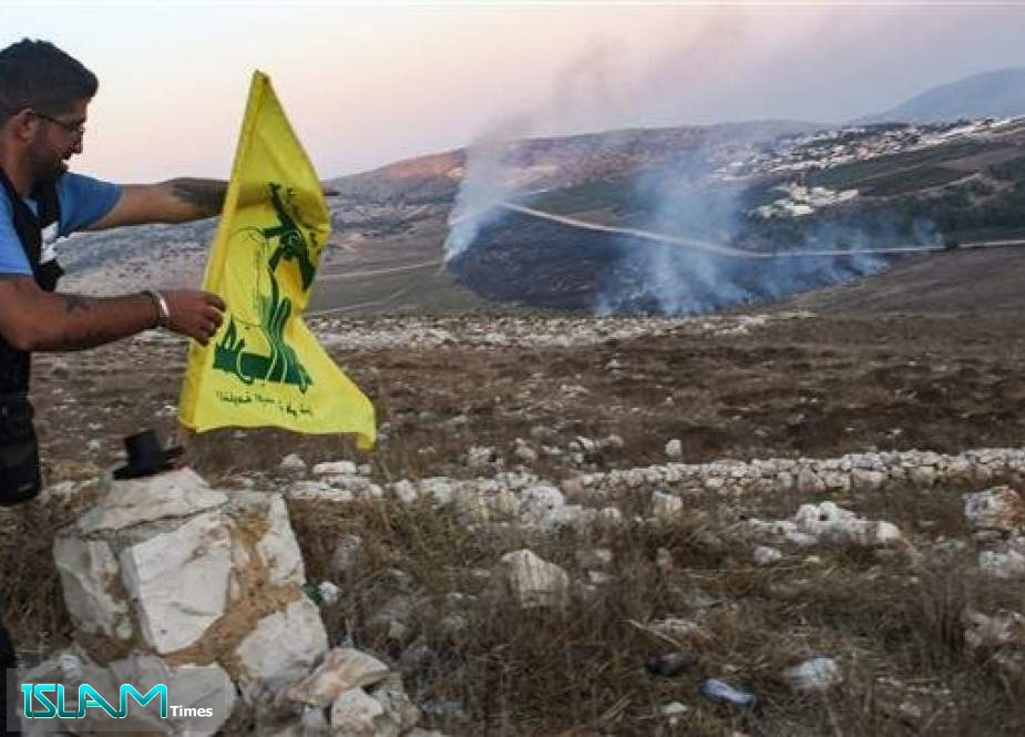 A man fixes the flag of the Lebanese Hezbollah resistance movement along a brick hedge in the Lebanese village of Maroun al-Ras along the southern border with the Israeli-occupied territories on September 1, 2019, as fires blaze on the Lebanese side along the border following an exchange of fire between Hezbollah fighters and the Israeli army.