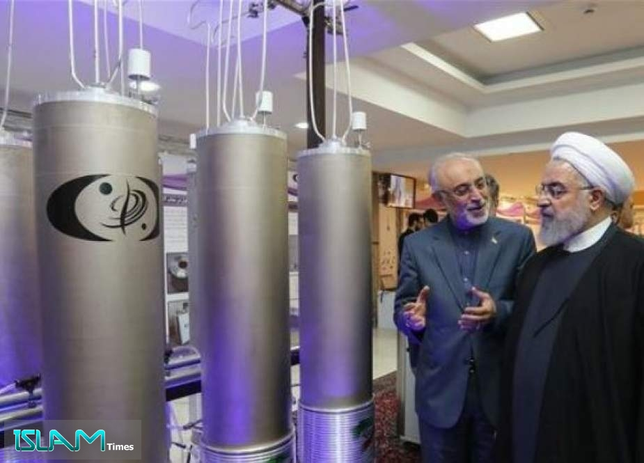 In this file handout photo taken on April 09, 2019 by Iran's presidential office, Iranian President Hassan Rouhani (2nd L) listens to Ali Akbar Salehi, head of the Atomic Organization of Iran (AEOI), inspect nuclear achievements on the country's National Nuclear Technology Day