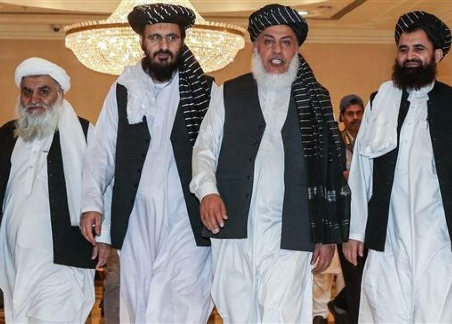 Taliban negotiators walking during the second day of Afghan talks in Doha, Qatar.jpg