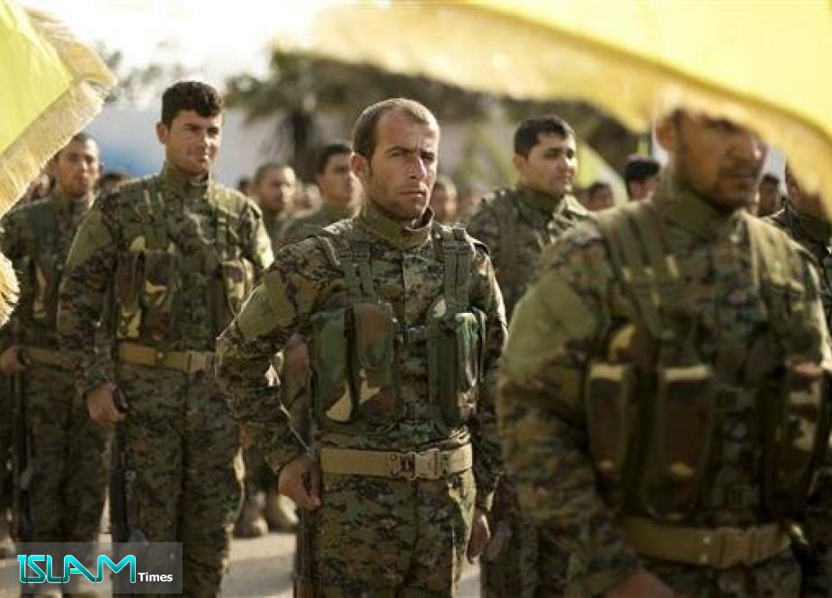US-sponsored and Kurdish-led militants from the so-called Syrian Democratic Forces (SDF) stand in formation at a ceremony to mark their defeat of the Daesh Takfiri terrorist group in Baghouz, at al-Omar Oil Field base, Syria, on March 23, 2019