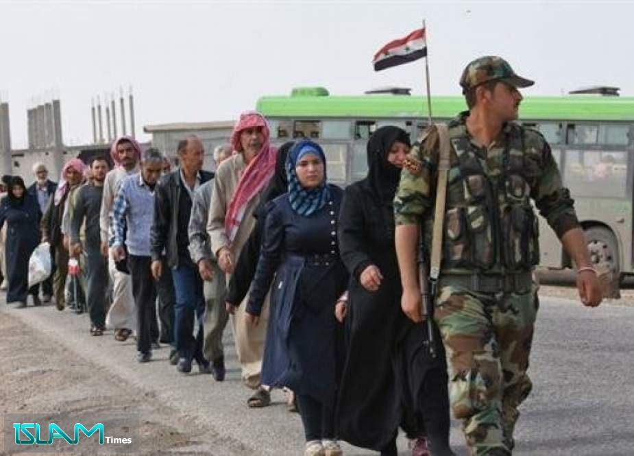 Syrian families walk as Syrian forces stand guard at the Abu al-Duhur crossing on the eastern edge of Syria