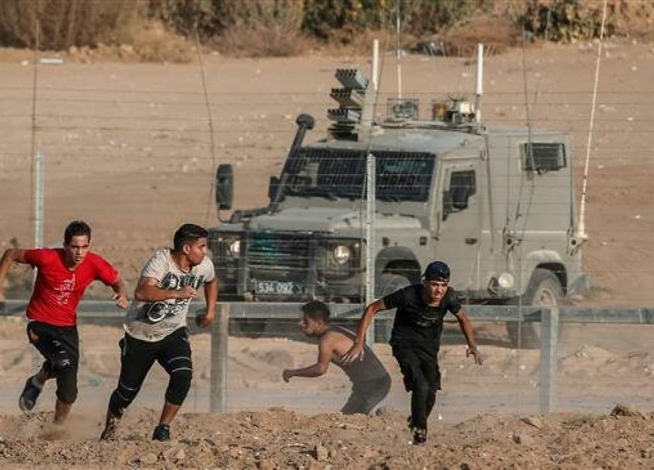 Palestinian protesters run for cover from Israeli forces.jpg