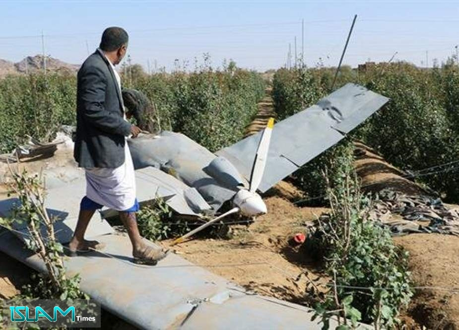 People inspect the wreckage of a drone aircraft reportedly downed by Houthi Ansarullah forces near the northwestern city of Sa'ada