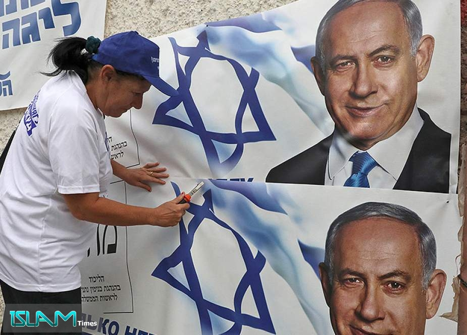 A woman places electoral banners for the Likud party showing chairman and Israeli Prime Minister Benjamin Netanyahu in the southern Israeli city of Beersheva