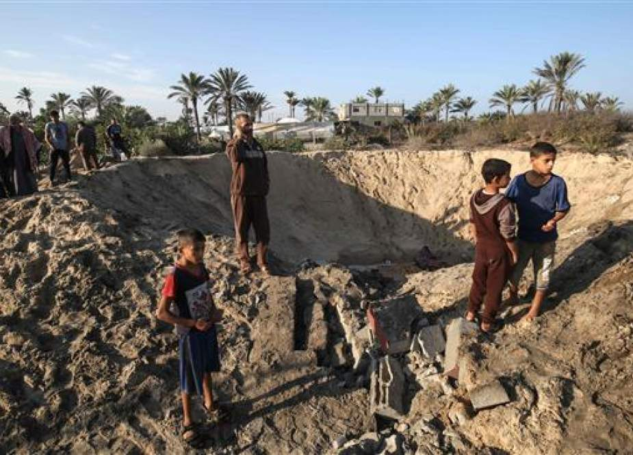 Palestinian children stand around a crater caused by an Israeli airstrike in Khan Yunis.jpg