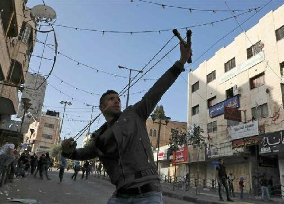Palestinian youth uses a slingshot to hurl a stone towards Israeli security forces.jpg
