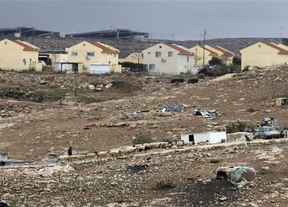 Tents and makeshift homes in which some Palestinian families live are pictured across an Israeli settlement.jpg