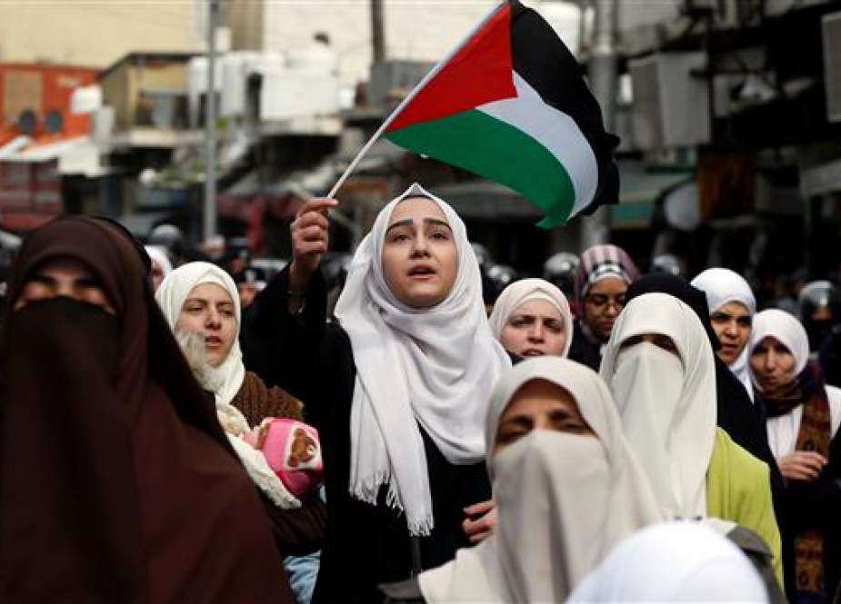 Woman holds the Palestinian flag and shouts slogans during a protest in Amman, Jordan.jpg