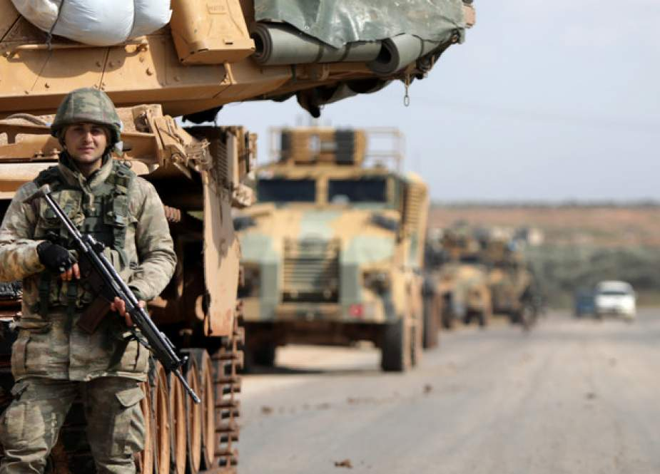 Turkish soldier stands in front of a military vehicles convoy.jpg