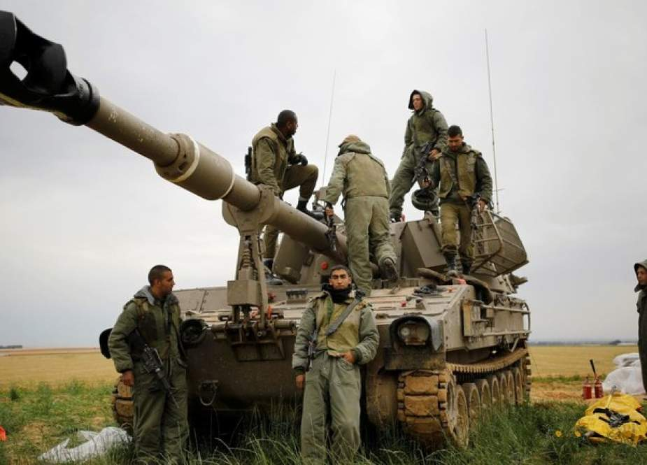Israeli soldiers stand on and around a mobile cannon near the border with Gaza.jpg