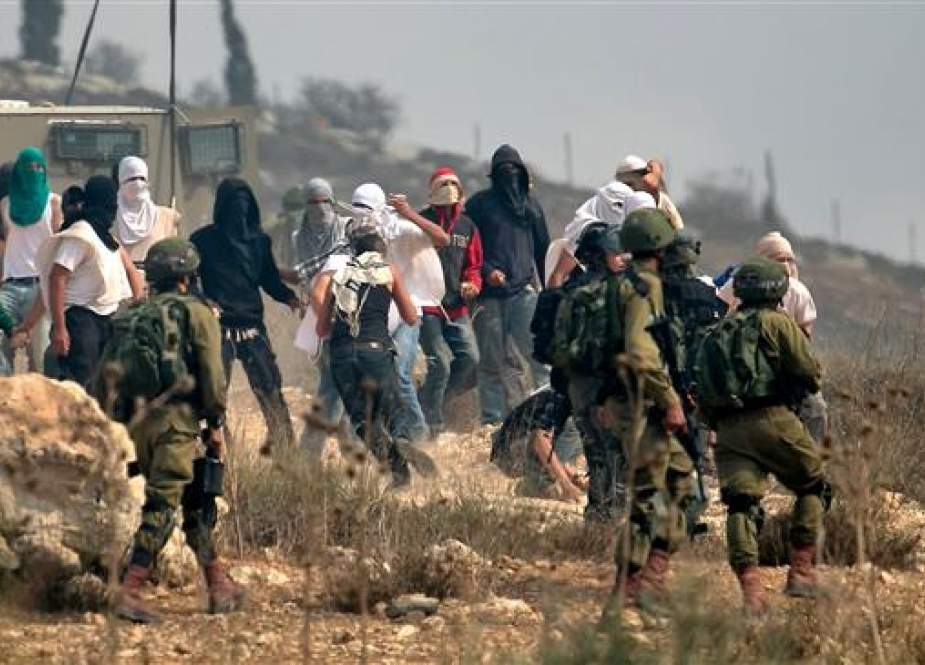 Israeli soldiers stand by as masked Israeli settlers throw stones at Palestinian protesters.jpg