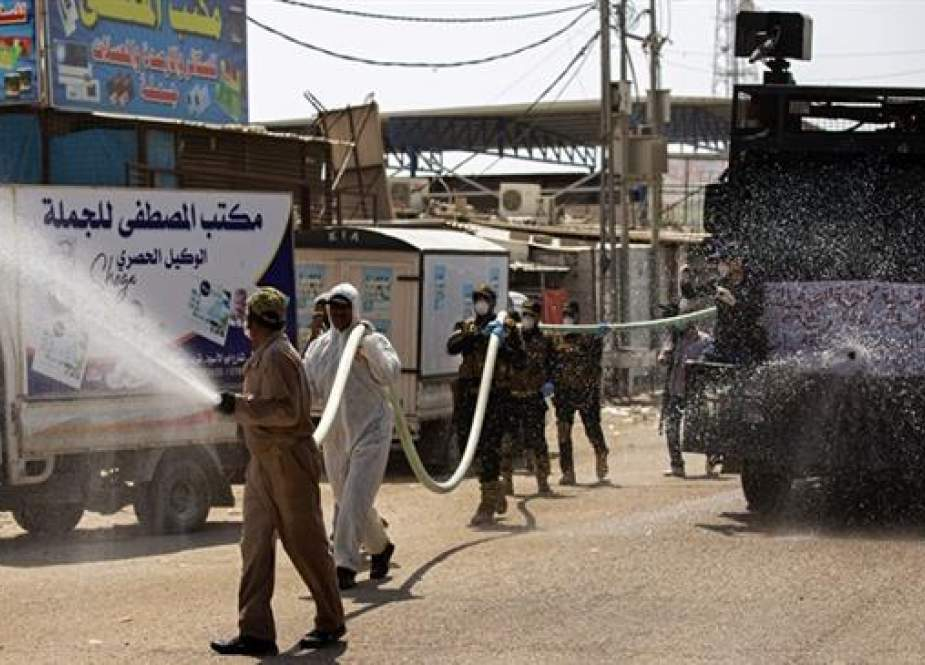 Iraqis use a water-cannon vehicle to spray disinfecting liquid in southern city of Basra.jpg