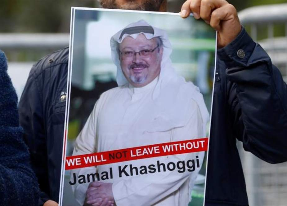 Demonstrator holds a picture of Jamal Khashoggi in front of Saudi Arabia