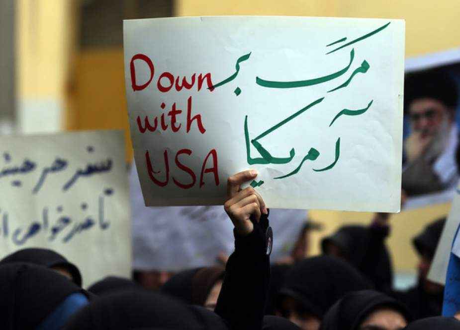 Iranian protester holds a placard reading