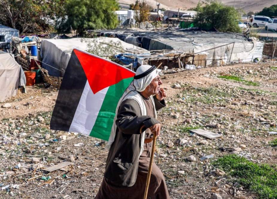 Bedouin man walks with a Palestinian flag in the village of Khan al-Ahmar, West Bank.jpg